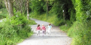 Three children running away from the camera along a gravel trail in the woods