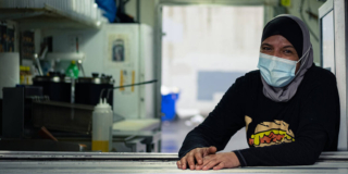 A woman wearing a head scarf and a mask sits in a commercial kitchen.