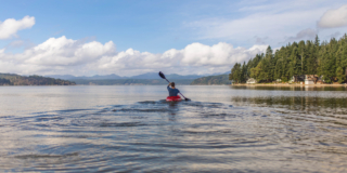 Person on kayak under blue and white sky