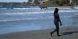 A female surfer in a wet suit walks on the shore carrying a surfboard over her head.