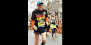 Ken Richardson running a marathon with a big smile on his face and wearing a Marathon Maniacs t-shirt.