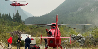 One red helicopter sits on the ground while people get ready to fly it. Another red helicopter has just taken off.