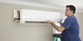 A man in a blue t-shirt installs a heat pump on a beige wall.