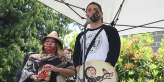Ken Watts speaks outside in front of a microphone. He is holding a drum and has a black handprint across his mouth. He is standing next to Cynthia Dick, who wears a woven cedar hat.