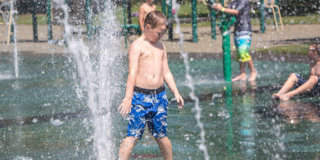A little kid in a blue swim suit gets sprayed with water in a splash park.