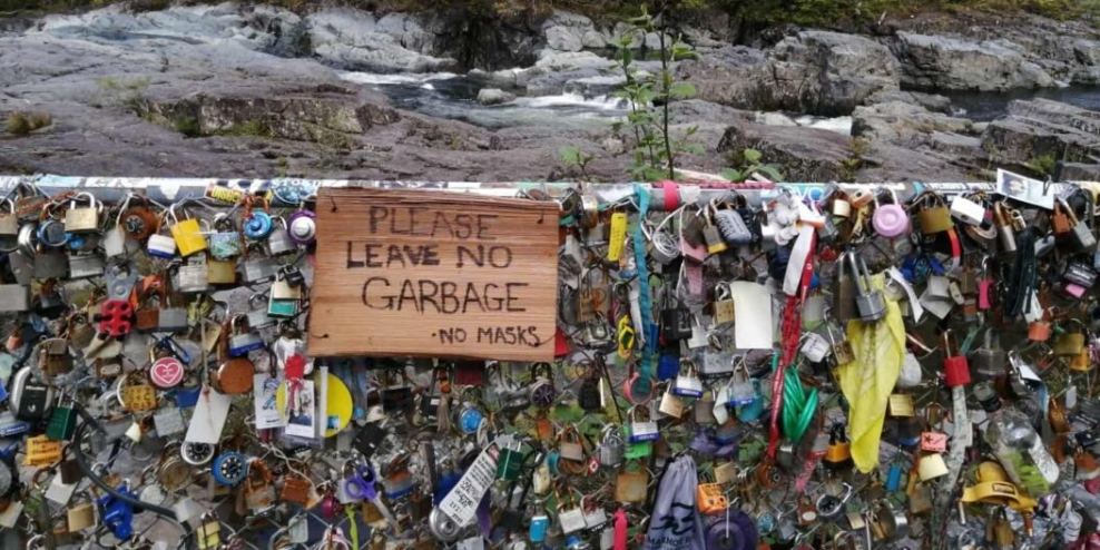 """A chainlink fence along Highway 4 is covered with locks and garbage. It has a sign that says """"please leave no garbage""""."""