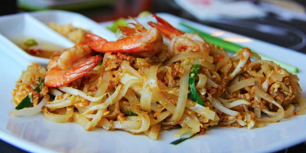 Pad Thai with shrimp on a white plate.