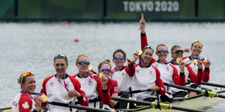 The Canadian Women's 8 rowing team in a row boat holding up their gold medals.