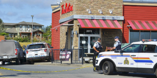 RCMP officers stand outside a Tim Horton's on a sunny day.
