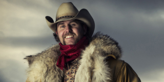 A portrait of Tim Hus in a cowboy hat and big fur coat.