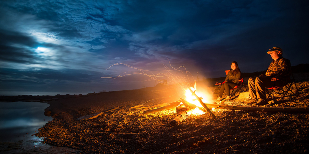 Two people sit by a campfire at night with the moon behind some clouds.