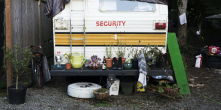 The back end of a camper van. It has plants in pots on the bumper. It looks like someone has lived here for a while.