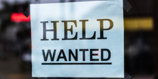 """A """"Help wanted"""" sign is taped inside a restaurant window."""
