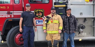 Three NorthIsle firefighters in front of a red fire truck.
