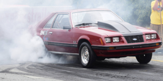 An old red sports car takes off from the starting line and leaves smoke behind the tires.