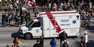 People with signs stand in the street in front of an ambulance with a patient in it.