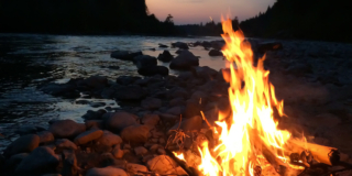 A campfire burns at sunset.