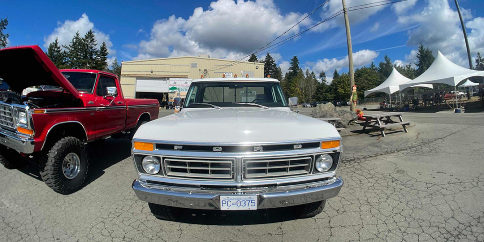The front of a vintage Ford F150 on a sunny day.