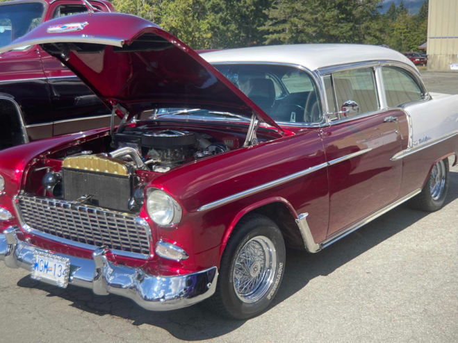 A red Bel Air with a white roof, parked with its hood popped up.