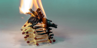 A toy house built out of matches burns in front of a pale green background.