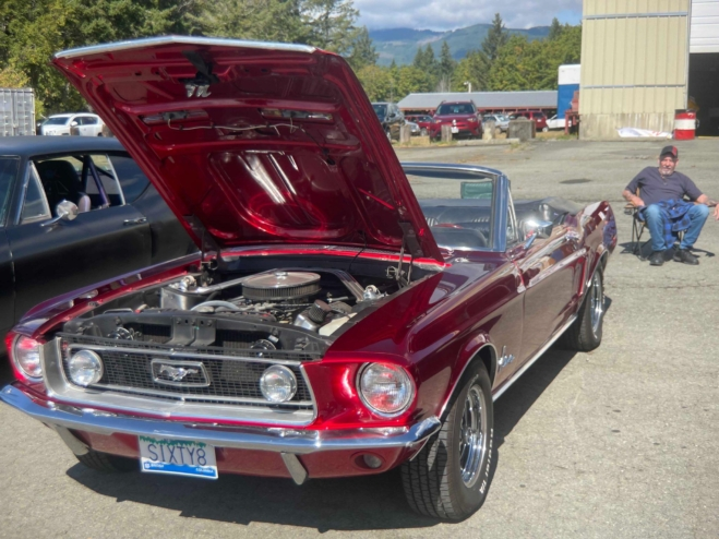 A red classic Mustang parked with its hood propped up.