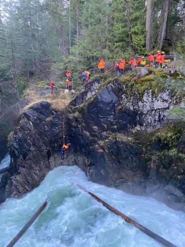 The Arrowsmith Search and Rescue team dangles a rescuer over a cliff into a raging river to bring an unconscious man out of the falls.