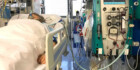 A woman lies in an ICU bed with wires and tubes hooked up to her body.