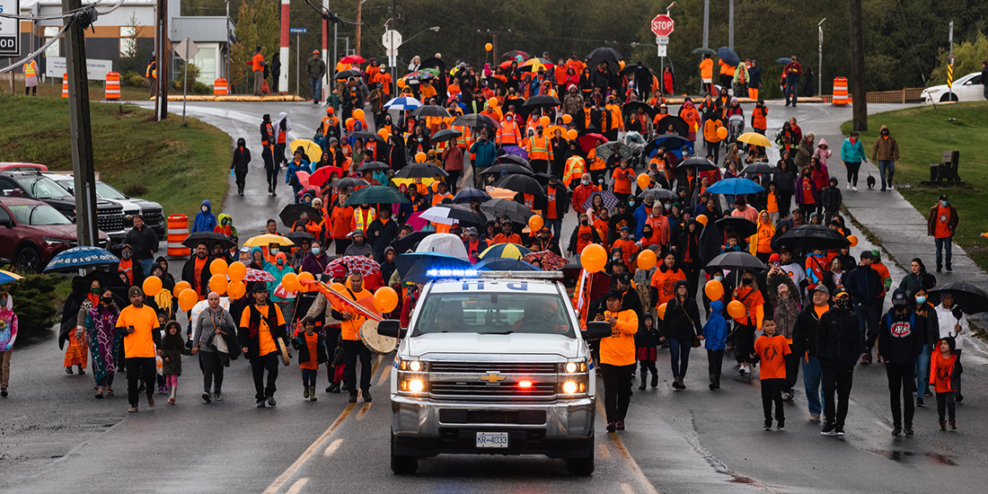 A large group of people in orange shirts march along a street behind a police vehicle in the rain.