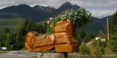 A photo of the big wooden boot that was carved using a chainsaw. There are mountains in the background.