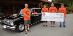 A group of smiling people stands in front of a shiny black car while holding up a huge novelty cheque.